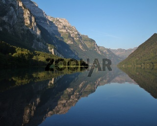 Summer morning at lake Klontalersee, Switzerland. Mountain range mirroring on the surface.