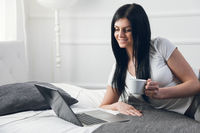 Relaxing on the bed. Beautiful young woman enjoying a cup of coffee and using her laptop