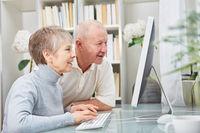 Paar Senioren schaut neugierig auf PC Monitor