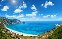 Petani Beach summer panorama (Kefalonia, Greece). Deep blue sky with cumulus clouds and sunshine.