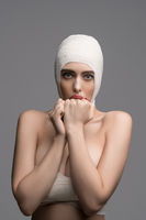 Frightened woman with bandaged head isolated shot