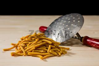 Passatelli original Italian pasta over a wooden background