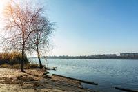 Autumn sunny landscape. Beach with a pier near the river