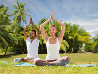 couple doing yoga in lotus pose outdoors