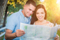 Happy Mixed Race Couple Looking Over A Map Outside Together.