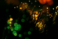 Abstract multicolored festive lights using a defocused bokeh effect with a black background. The sparkling colored lighting is created from the blur of intense Christmas decorations.