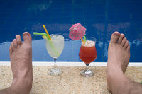 Cocktails and male's feet at the edge of the outdoor pool