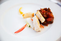 white fish with stewed eggplant garnish on plate