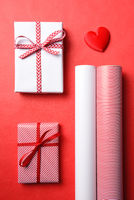 Two Wrapped presents with matching paper rolls and a red heart.