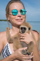 Woman with monkey on the beach