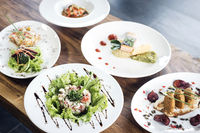 mixed modern gourmet fusion food dishes on table