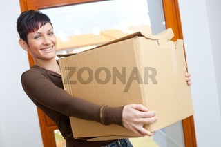 Young woman lifting cardboard box