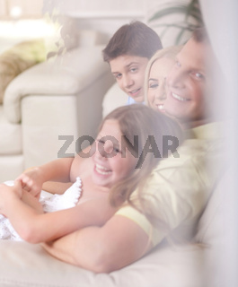 Happy family smiling and looking  behind the window glass in living room