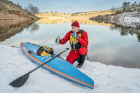 Hot tea break during winter paddling on stand up paddleboard in Colorado