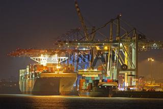 Ein Containerschiff liegt bei Nacht im Hamburger Hafen, Containerterminal Tollerort, Hamburg, Deutschland