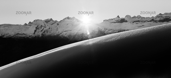 Beautiful monochrome sunrise in snowy mountain landscape. Sunbeams illuminating unspoiled powder snow. Alps, Switzerland.