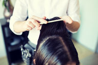male stylist hands combing wet hair at salon