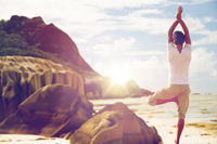 man meditating in yoga tree pose over beach