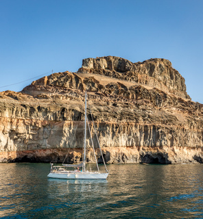 Gran Canaria, Canary Islands in Spain: Sailboat at rest in the ocean in front of mountains at the coast at Puerto de Mogan