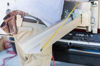 Worker Measuring Rain Gutter Processing Through Seamless Shaping Machine