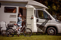 Woman on electric bike resting at the campsite VR Caravan car Vacation.