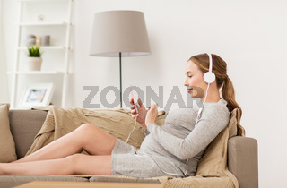 pregnant woman with smartphone and headphones