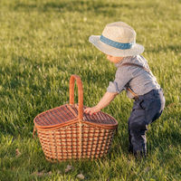 Toddler child outdoors. One year old baby boy wearing straw hat with picnic basket