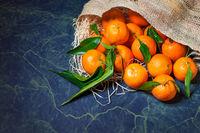 Fresh mandarins stacked on hessian sack