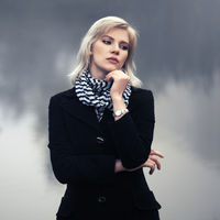 Young fashion woman walking by the lake in a fog