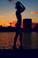 Portrait of young woman as silhouette by the river. Slim sporty girl is posing in river embankment in front of red sunset