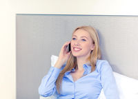 happy businesswoman with smartphone in hotel room