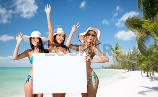 happy young women with white board on summer beach