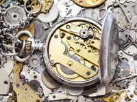 open silver pocket watch on heap of spare parts