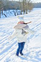 Kleines Mädchen tanzt und spielt im Winter