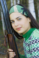 Portrait of a hunter girl with a gun