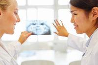 Frauen als Ärzte besprechen ein Röntgenbild