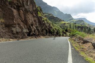 Asphaltierte Straße mit Kurve im Gebirge