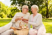 senior couple with strawberries at picnic in park