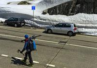 Fussgänger mit Ski und Autos auf der Passhöhe