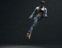 Girl in jeanswear jumping gracefully in the dark
