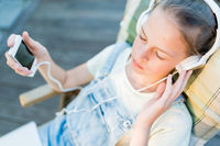 Closeup of pretty teen girl in headphones listening to music using a laptop outside on the terrace in the garden