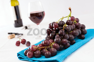 Closeup of a bunch of red grapes and a glass of red wine with a wine bottle on background