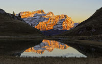 Massif Les Diablerets in the evening light is mirrored in a mountain lake, Switzerland