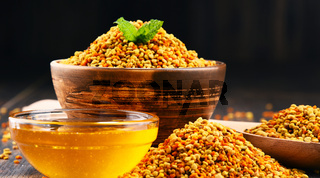 Bowls with bee pollen and honey on kitchen table. Nutritional supplements