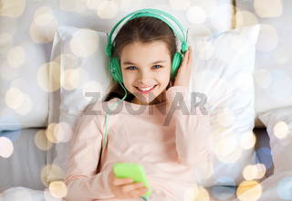 girl with headphones listening to music in bed