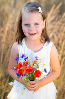 Cute little girl with wild flowers red poppy bouquet in the summer meadow
