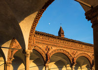 Grand Cloister of the Pavia Carthusian monastery at sunset with moon.