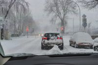 A car stands in the snowstorm in front of closed railway barriers.