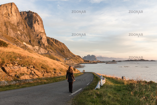 Woman walking on a road in Lofoten