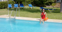 Lifeguard in red swimsuit sitting at edge of pool